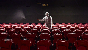 A Worker Sanitizing theater room for safety measure.