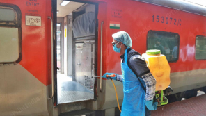 Train coaches being sanitized by the worker.
